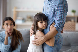 Small child hugging her father with mother looking on at them both. Attachment issues and trauma as a child can have adverse effects if not treated. Get help in Ewing, NJ at Mindful and Multicultural Counseling